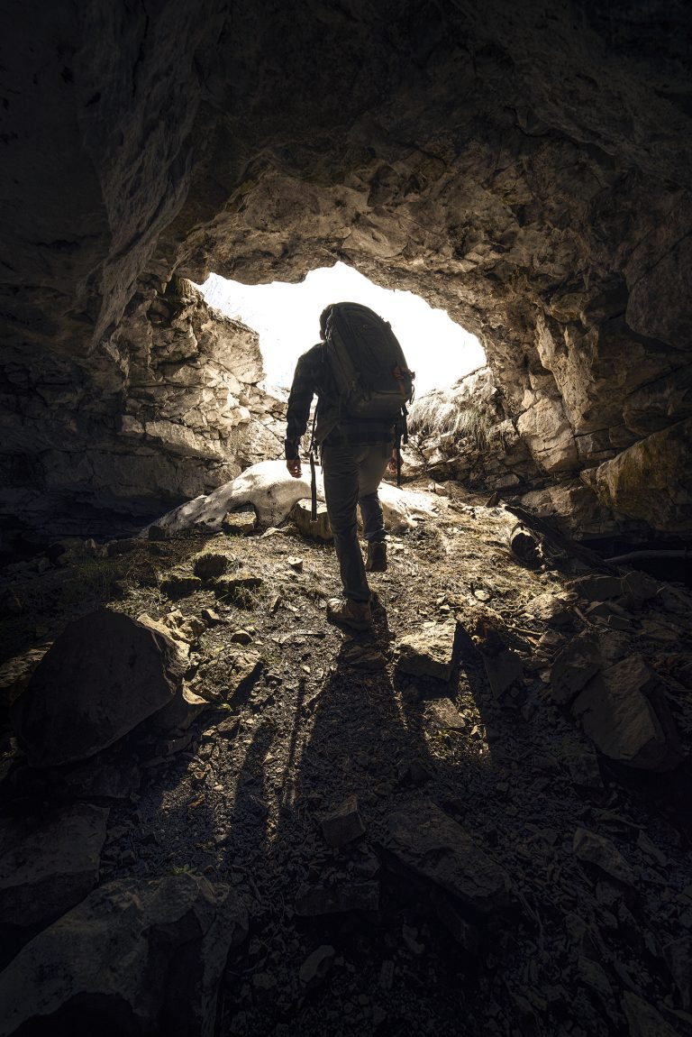 A caver with a pack walking towards the entrance of a Black Hills Cave